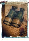 Old antique vintage binoculars field glasses on wicker basket. Old antique brass and green colored vintage binoculars field glasses on wicker basket Royalty Free Stock Image