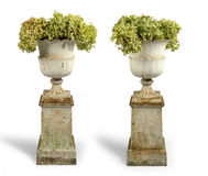 Old antique cast iron painted garden urns on plinths isolated on Royalty Free Stock Photo