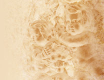 Old Antique Cherub Background. Two cherubs are on a stone wall and they are faded on a light brown gold background. The background is old, worn and textured Royalty Free Stock Image
