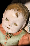 Old antique childs doll with creepy face. Old antique child's doll with creepy face, cracked and worn, has seen better days Royalty Free Stock Photography