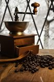 Old antique coffee grinder with coffee beans on a wooden windowsill. Blurred image of the winter landscape outside the window stock images