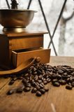 Old antique coffee grinder with coffee beans on a wooden windowsill. Blurred image of the winter landscape outside the window stock photos