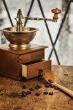 Old antique coffee grinder with coffee beans on a wooden windowsill. Blurred image of the winter landscape outside the window royalty free stock photo
