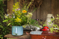 Old antique cooking pots with a bunch of flowers in the garden. Royalty Free Stock Photos