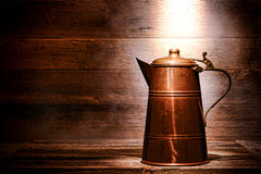 Old Antique Copper Water Pitcher in Ancient House. Old and antique vintage copper water pitcher or coffee pot with handcrafted brass handle on aged wood boards Stock Image