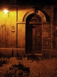 Old antique door at night. An old, shadowy antique door under a golden light at night Royalty Free Stock Image