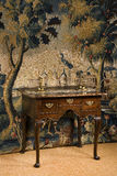 Old antique European lowboy dresser against period tapestry Stock Photography