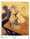 Old antique fan with metal blades sitting on table. With shadows Royalty Free Stock Photography