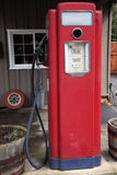 Old antique gas pump in front of auto business Royalty Free Stock Images