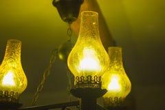 Old antique kerosene oil lantern brass hurricane lamp with hot burning flame casting light Stock Photo