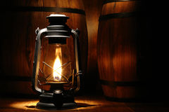 Old Antique Kerosne Oil Lantern Burning. Old-fashioned black kerosene oil lantern light with intense glowing flame burning near old distressed aged wood barrels Stock Image