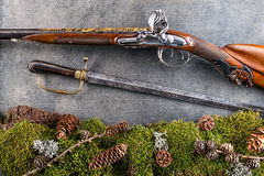 Old antique long gun and old saber with forest still life on grey background, historical weapons Royalty Free Stock Images