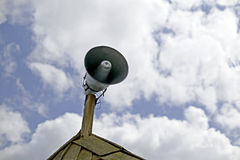 Old antique loudspeaker on the roof. Cloudy sky background Royalty Free Stock Images