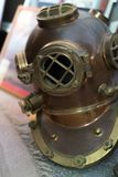 Old antique metal scuba helmet on the ground. Historic copper aqualung for diving in the ocean water royalty free stock photos
