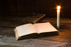 Old antique opened book with burning candle near on the wooden table. Stock Photos
