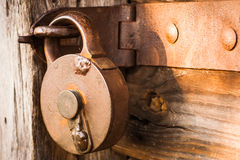 Old antique padlock. Old and antique locked padlock on wooden door, representing concept of security Stock Image