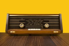 Antique radio on a yellow background with dark brown wooden. Old antique radio on a yellow background with dark brown wooden table Royalty Free Stock Image