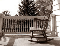 Old Antique Rocking Chair on an Old House Porch. Old antique wood rocking chair on a historic house porch in nostalgic sepia Stock Photography