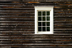 Old Antique Sash Window on a Historic House Wall. Antique sash window on the aged weathered wood clapboard wall of an old historic house Stock Photos