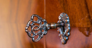 Old antique skeleton key in lock of wooden cabinet Stock Images