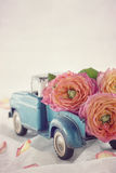 Old antique toy truck carrying a roses stock photo