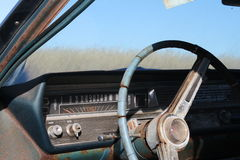 Old antique vintage retro rustic rusty dirty car steering wheel dashboard window outdoors in a field. Royalty Free Stock Image