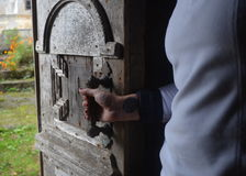 Old antique wood door. Woman hand opening an old house wood door Royalty Free Stock Image
