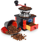 Old antique wooden black and red coffee grinder, cup and spilled. Old antique wooden coffee grinder. Coffee mill hand-painted in black, red and blue. Next to the royalty free stock images