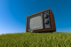 Old antique wooden TV on grassy hill Stock Photography
