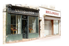 Old antiques shop exterior. High  key image of old antiques shop  next to bakery in France Stock Images