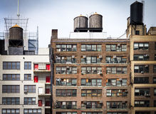 Old apartment buildings background in New York City. Old vintage apartment buildings with wall of windows and water towers on the roof tops in downtown New York Royalty Free Stock Image