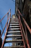 Old Apartment Emergency Stairs. View up a set of old steel apartment emergency exit stairs for a yellow brick building Royalty Free Stock Image