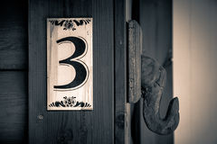 Old apartment number sign on the wall of wood with the number three on it.  Royalty Free Stock Image
