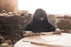 Old Arab woman prepares bread. HURGHADA, EGYPT - MAY 2015 - Old Arab woman prepares bread in a Bedouin village Royalty Free Stock Image