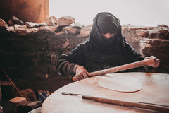 Old Arab woman prepares bread Stock Photos