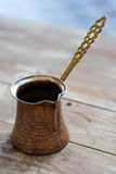 Old Arabic coffee pot on a wooden table. This Lebanese Arabic coffee pot is used to boil and serve finely ground coffee beans in the Turkish and Arabic tradition Royalty Free Stock Images