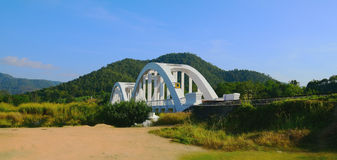 Old arch bridge across the creek in LAMPHUN THAILAND. White colo Stock Photo