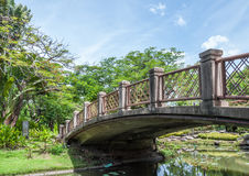 Old arch bridge. Is crossing the small pond of city park Stock Photo