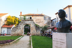 Old Arch in Dobrile Juraj Square. POREC, CROATIA - JULY, 14: Old Arch and monument dedicated to the Catholic bishop Dobrile Juraj on July 14, 2017 royalty free stock photo