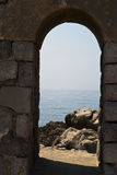 Old arch with sea and rocks in Cefalu. Sicily stock photography