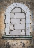 Old arch window covered with bricks. Old arch window covered with bricks and cracked wall Royalty Free Stock Image