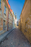 Old archaic narrow street in medieval downtown. Small narrow corridor time street with church on background Stock Photo