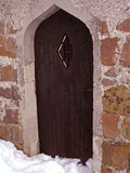 Old arched church door at winter time. Old arched chapel door and wheathered facade at winter time Stock Photography