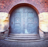 Old arched door and steps. Steps with a handrail leading to an old steel arched double door in a brick building facade