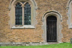 Old arched doorway 2. Arched doorway and windows of an old church at Rushden, Hertfordshire, UK. Weathered carved stone faces as architectural details Stock Photography
