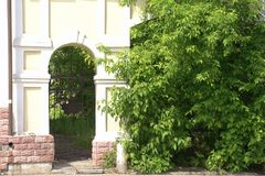 Old arched passage in a brick wall among green trees royalty free stock photos