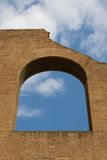 Old arched window. And brick wall against a blue sky with clouds Stock Images
