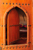 Old arched wooden doorway. An old wooden door with metal studs and an arched carved frame stands open Royalty Free Illustration