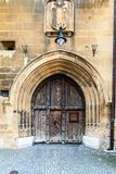Old arched wooden medieval door with blazon Royalty Free Stock Image