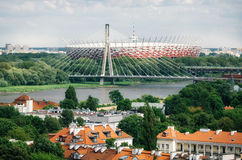 Old architecture, bridge, Vistula river, National Stadium in Warsaw. Cityscape of Warsaw. Old architecture with red roofs on the foreground, Holy Cross Bridge Royalty Free Stock Image